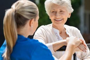 Persona atesa mirant a la cuidadora, atenció centrada en la persona
